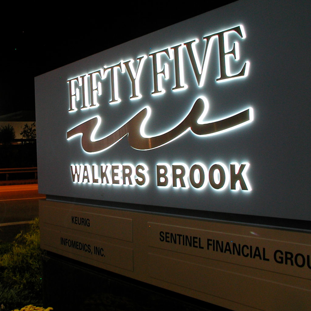 At night, the sign to 55 Walkers Brook is lit up to guide visitors into the industrial park.