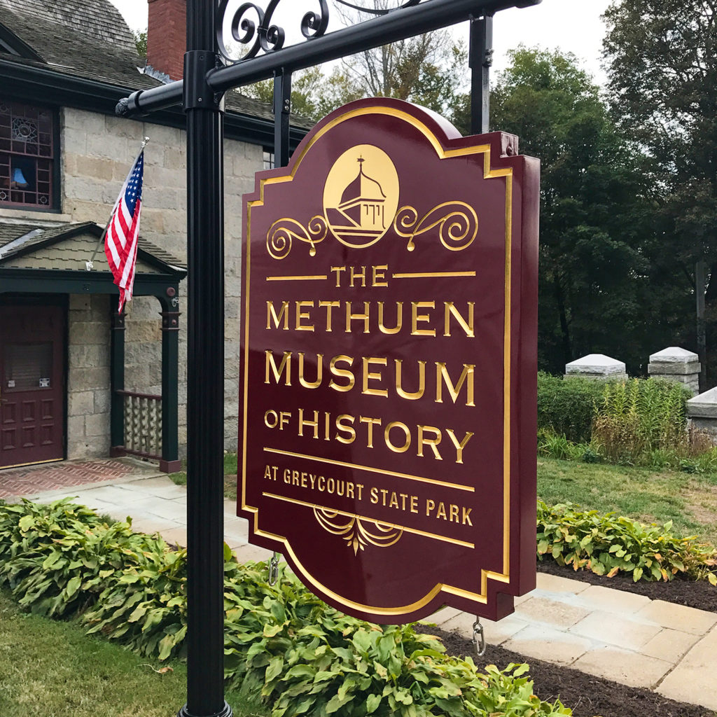 A beautifully engraved hanging sign welcomes guests to The Methuen Museum of History at Greycourt State Park in Methuen.