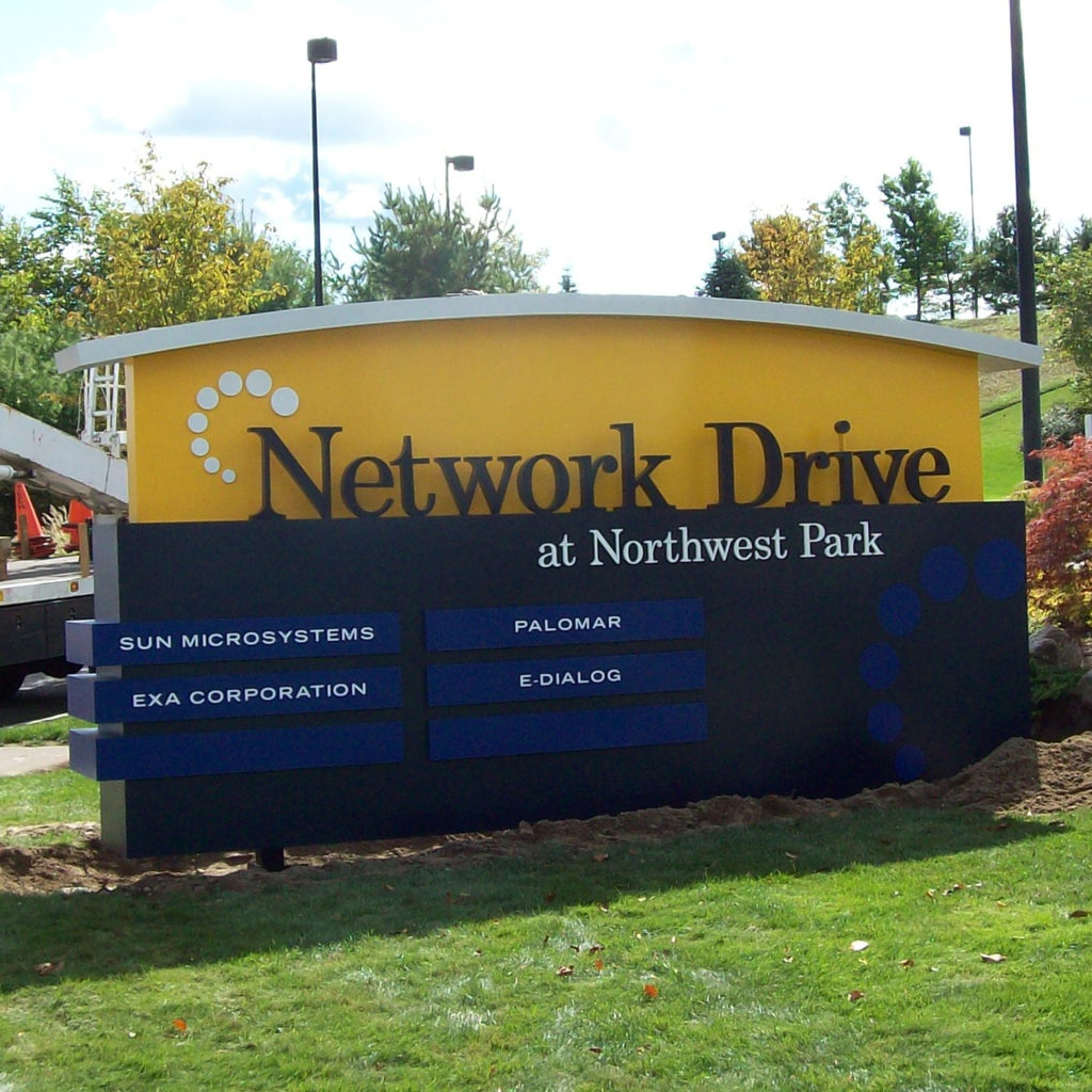 A large, outdoor sign at Network Drive at Northwest Park greets guests and employees of Sun Microsystems, EXA Corporation, Palomar, and E-Dialog.