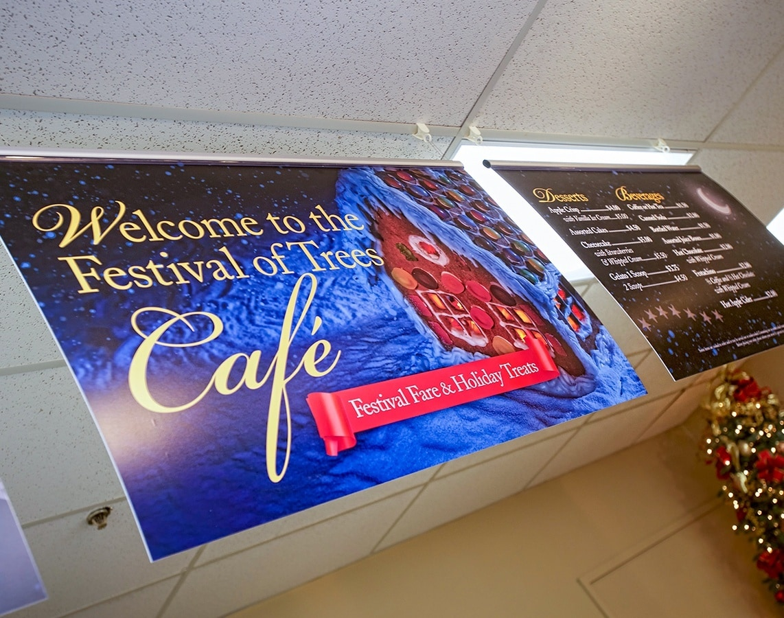 Hanging welcome signs and menu options greet guests in the cafeteria at the Festival of Trees in Methuen, Massachusetts.