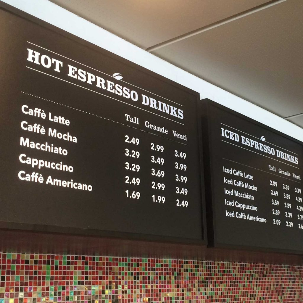 Hot and cold espresso drink menus are displayed overhead for guests in the NexDine cafeteria.