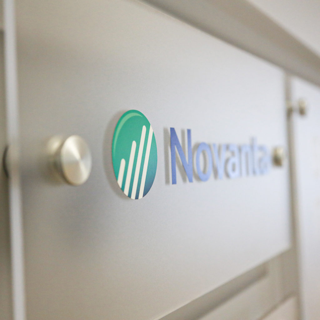 A Novanta logo sits on a clear plexiglass display to greet guests in the front lobby of their Bedford, MA facility.