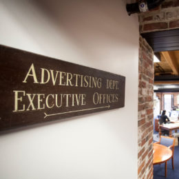 A sign directs visitors to the Advertising Department and Executive Offices at The Simon Group.