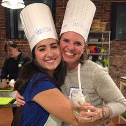 Two employees enjoy a team-building event at a local cooking studio.