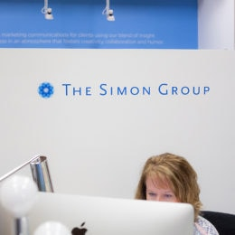 An employee is typing on a Mac in the lobby of The Simon Group.