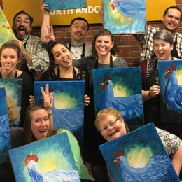 Colleagues show off their masterpieces at a local paint night event.