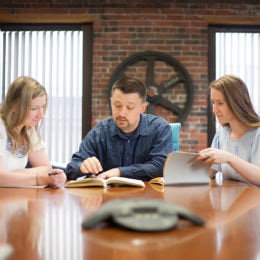 A group of colleagues compares notes and discusses the next marketing communications project.